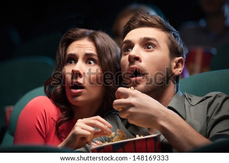 Horror movie. Terrified young couple eating popcorn while watching movie at the cinema - stock photo