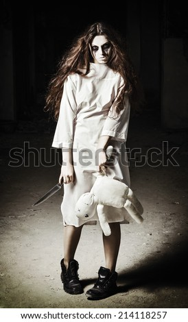 Horror scene: a scary monster girl with moppet doll and knife in hands - stock photo