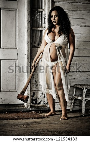 Horror Scene of a Pregnant Woman holding an Axe at front door of an old house - stock photo