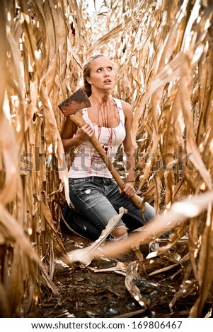 Horror Scene of a Pretty Blonde Woman Holding an Axe in a Corn Field  - stock photo