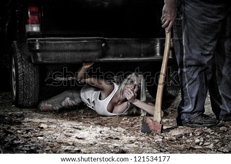 Horror scene of a woman hiding under a truck from a man dragging an Axe - stock photo