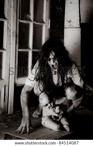 Horror Scene of a Woman Possessed Crouching with a doll by a window - stock photo