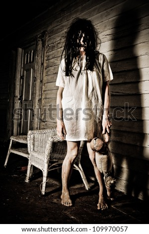 Horror Scene of a Woman Possessed holding a doll - stock photo