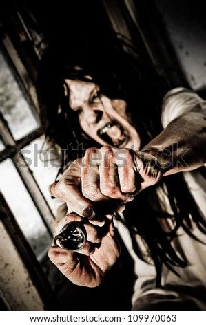 Horror Scene of a Woman Screaming Defending herself with a Cork Screw Focus is on Cork Screw - stock photo