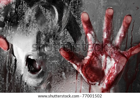 Horror Scene of a Woman with Bloody Hands against Wet Glass - stock photo