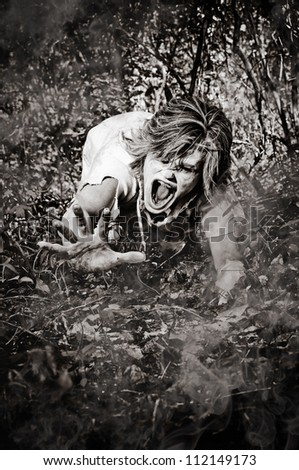 Horror Scene of a Zombie Crawling though woods - stock photo