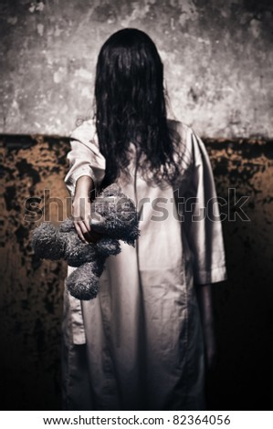 Horror scene with girl in a white robe with a bear in his hand - stock photo