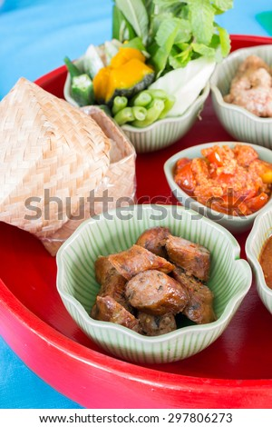 Hors-d'oeuvre ,Thai food Northern style (Khan-Toke) : spicy minced pork salad, thai sausages, deep fried pork skin, spicy chilly paste, sticky rice - stock photo