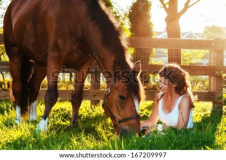horse and beautiful, wholesome  woman in pasture - stock photo