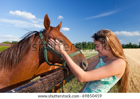 horse and blond girl in paddock on summers day - stock photo