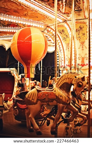 horse and bulb on night carousel - stock photo