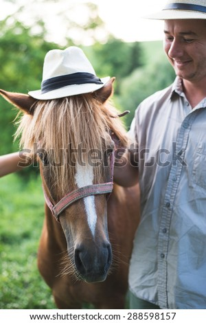 Horse and man in panama hat - stock photo