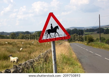 horse and rider sign by country road - stock photo