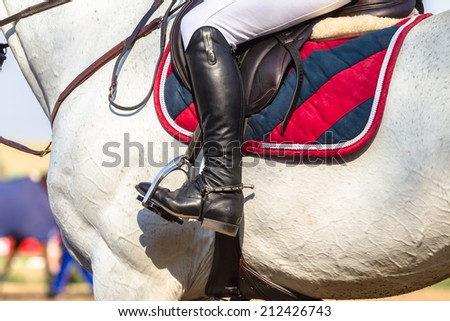 Horse Boot Saddle Rider Accessories,  Equestrian Horse rider close-up saddle cover boots horse accessories - stock photo