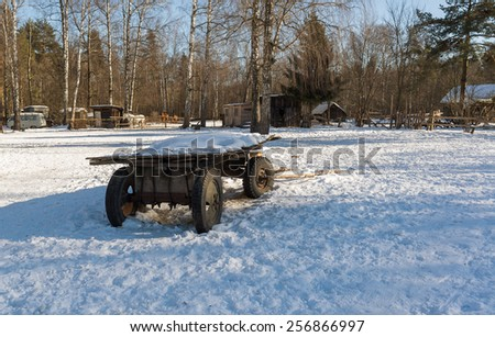 Horse carriage with car wheels and shafts that lie ahead in the snow against the background of the ranch with a shelter for horses. Moving rays low winter sun the snow creates light and shadow pattern - stock photo