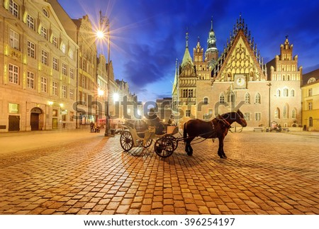 Horse carriages at market square in Wroclaw near the town hall in the night. Poland - stock photo