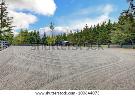 Horse farm gravel open arena with small shed and black fence. - stock photo