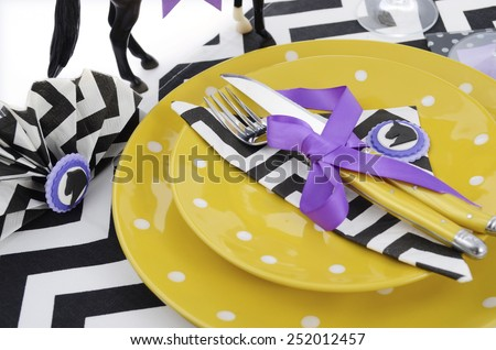 Horse racing carnival event luncheon table place setting in purple, yellow theme, and black and white chevron strip table runner, closeup. - stock photo