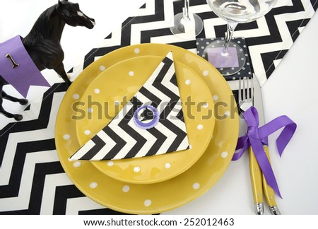 Horse racing carnival event luncheon table place setting in purple, yellow theme, and black and white chevron strip table runner, overhead. - stock photo