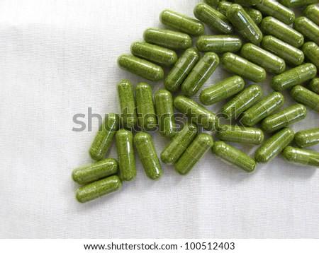 Horse radish leaves crushed into the capsule on white cloth - stock photo