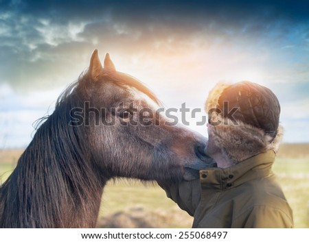 Horse rested her head on  shoulder of man - stock photo