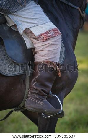 Horse rider leg saddle leather details closeup - stock photo