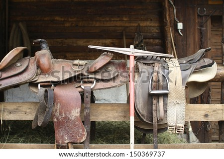 horse saddles on a wooden fence - stock photo