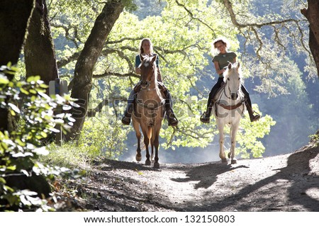 Horseback riders; two attractive women ride horses with backlit leaves behind them - stock photo