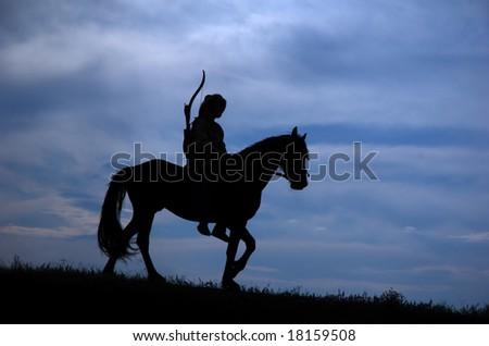 Horseman riding on the sunset - stock photo