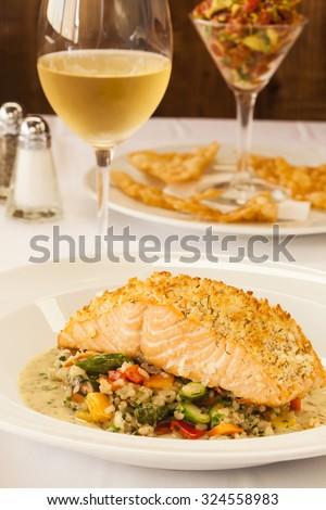 horseradish-dill crusted Scottish salmon with whole-grain mustard sauce, tuna tartare appetizer and a glass of chardonnay - stock photo