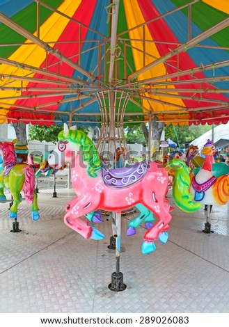 Horses on a carnival Merry Go Round in temple fair - stock photo