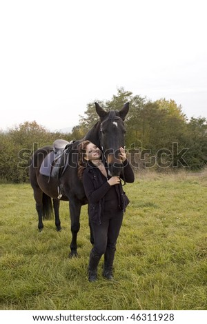Horsewoman and horse stand in a meadow on a background of shrub. - stock photo