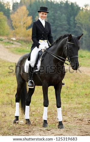 horsewoman jockey in uniform riding horse outdoors - stock photo