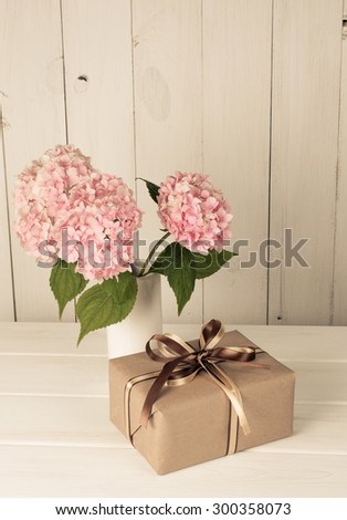 Hortense in vase and gift box on wooden board in shabby chic style - stock photo