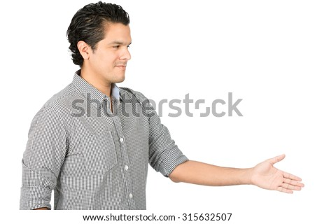 Hospitable, good looking hispanic man in casual button down shirt extending, offering handshake looking directly at camera, greeting warmly with a caring, friendly smile. Horizontal half-length - stock photo