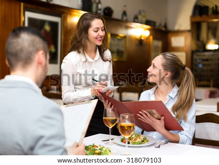 Hospitable waitress taking an order from a couple in a rural restaurant - stock photo