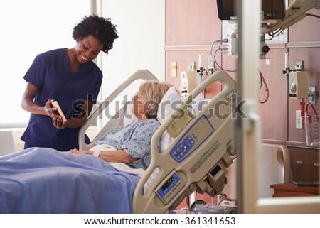 Hospital Nurse With Digital Tablet Talks To Senior Patient - stock photo
