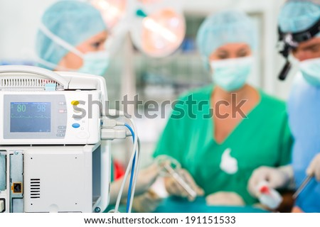 Hospital - surgery team in the operating room or Op of a clinic operating on a patient in emergency situation - stock photo