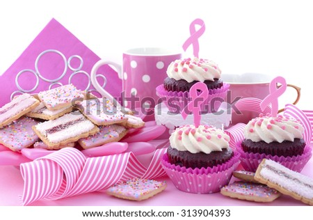 Host an Event for Pink Ribbon Day charity for womens breast cancer awareness with a pink morning tea with cupcakes, cookies, coffee and tea. - stock photo