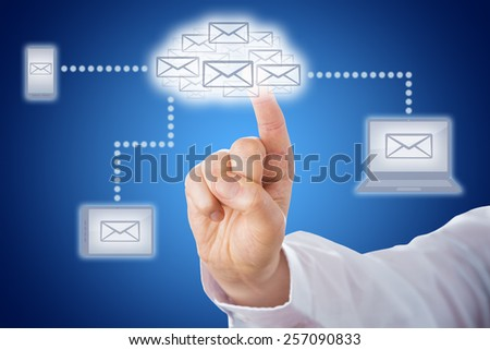 Host of email icons shaping a cloud symbol. The cloud computing icon does link to mobile devices that display a letter icon. Index finger of a business man is touching the cloud icon. Blue background. - stock photo