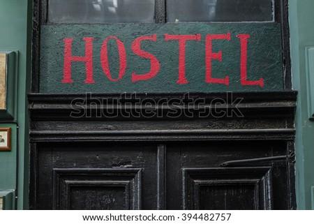 Hostel signboard on the old vintage door - stock photo