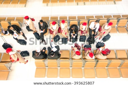 Hostesses and stewards top view at departures gate ready to flight at international airport - Airline company crew sitting before embark on plane - Radial zoom defocusing with focus on low right side - stock photo