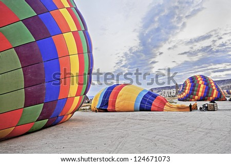 Hot air ballons laid flat on the surface, making ready for the next flights. Location of generic shot is Cappadocia Turkey - stock photo