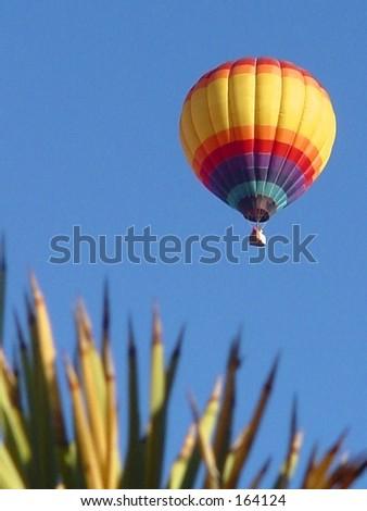 Hot air balloon against blue sky in desert - stock photo