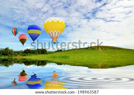 Hot air balloon floating in the sky over green grass with reflection water - stock photo