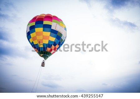 Hot air balloon floating in the sky over land - stock photo