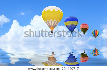 Hot air balloon floating in the sky with water reflection - stock photo