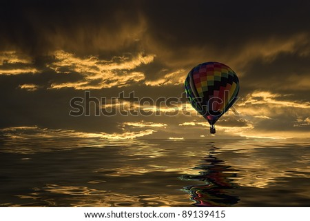 Hot air balloon floating over a lake at sunset. - stock photo
