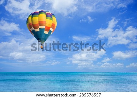 Hot air balloon fly over the sea with clouds blue sky background - stock photo