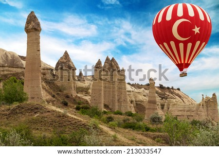 Hot air balloon flying over Love valley in Goreme Cappadocia, Turkey - stock photo